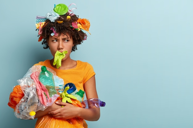 Wütende dunkelhäutige frau hat gummihandschuhe im mund, grinst im gesicht und ist gegen plastikverschmutzung Kostenlose Fotos