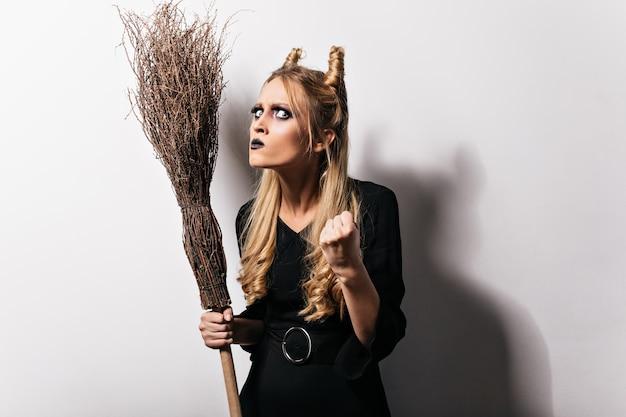 Wütende junge hexe mit besen hebt die faust. foto des blonden mädchens mit dunklem make-up trägt halloween-kostüm. Kostenlose Fotos