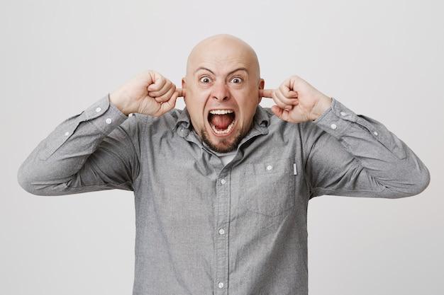 Wütender störender glatzkopf schloss die ohren mit den fingern, verfluchte laute nachbarn und schrie Kostenlose Fotos