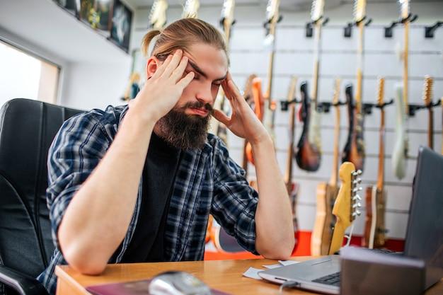 Wütender und müder junger hipster sitzen am tisch im zimmer. er hält die hände nahe am kopf. guy hat kopfschmerzen. viele e-gitarren hängen hinter ihm. Premium Fotos