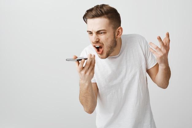 Wütender verärgerter kerl, der den mobilen lautsprecher anschreit, wütende sprachnachricht aufzeichnen Kostenlose Fotos