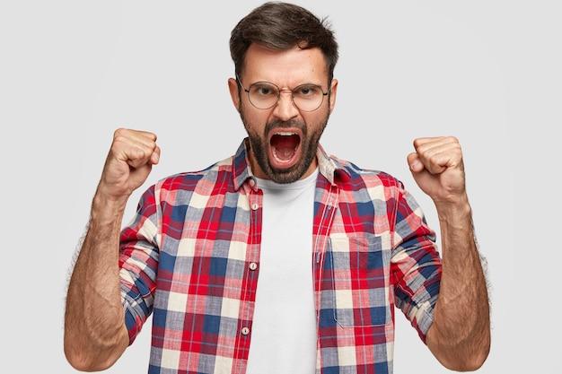 Wütender wütender mann mit gereiztem gesichtsausdruck, ballt wütend die fäuste, schreit jemanden an, trägt ein kariertes hemd, steht an der weißen wand. negative menschliche emotionen und gefühle. körpersprache Kostenlose Fotos