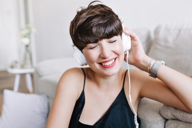 Wunderbare frau mit glänzendem braunem haar genießt lieblingsmusik mit geschlossenen augen und lächeln, das neben sofa sitzt Kostenlose Fotos