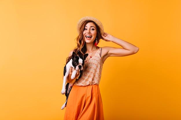 Wunderbares ingwermädchen im sommerhut, der glück während des porträtschießens mit hund ausdrückt. erstaunliches hübsches mädchen, das bulldogge hält und lächelt. Kostenlose Fotos