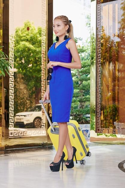 Wunderschöne attraktive junge asiatische frau mit kleinem koffer, der schickes hotel verlässt Premium Fotos