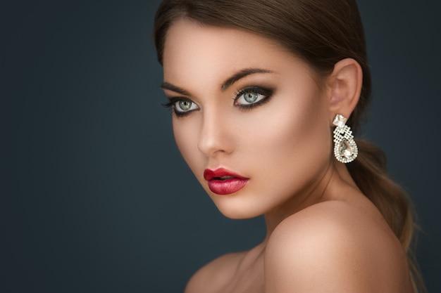 Wunderschöne frau mit luxusohrringen Premium Fotos