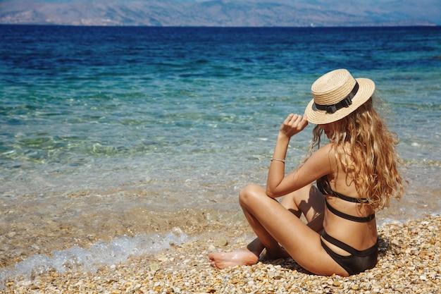 Wunderschöne frau sitzt am strand mit herrlichem meerblick Premium Fotos
