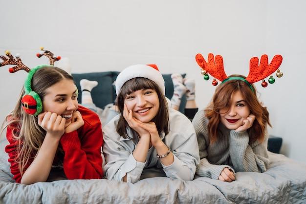 Wunderschöne lächelnde freunde, die spaß haben und pyjama-party genießen Kostenlose Fotos