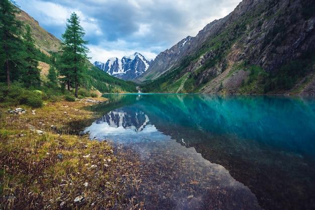 Wunderschöner bergsee mit blick auf den riesengletscher. erstaunliche riesige berge mit nadelwald. lärche am wasserrand. morgenlandschaftsmajestätische natur von hochländern. bewölkte berglandschaft. Premium Fotos