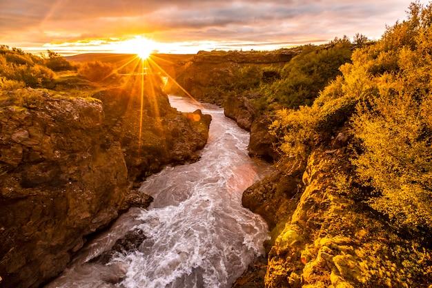Wunderschöner sonnenuntergang auf der holzbrücke des barnafoss-flusses, island Premium Fotos