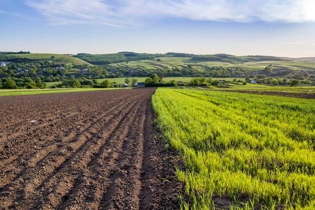 Wunderschönes friedliches frühlingsweites panorama aus gepflügten und grünen feldern, beleuchtet von der morgensonne, die sich unter klarem himmel auf fernen hügeln und im dorf bis zum horizont erstreckt. landwirtschaft und landwirtschaftskonzept. Premium Fotos