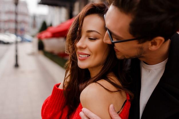 Wunderschönes verliebtes paar, das im freien umarmt und flirtet. romantische momente. hübscher mann, der auf seine hübsche freundin schaut. Kostenlose Fotos