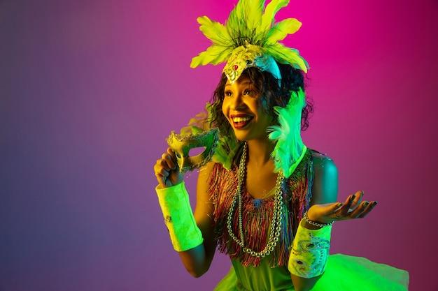 Wunderte sich. schöne junge frau im karneval, stilvolles maskeradenkostüm mit federn, die auf gradientenwand in neon tanzen. konzept der feiertagsfeier, der festlichen zeit, des tanzes, der party, des spaßes. Kostenlose Fotos