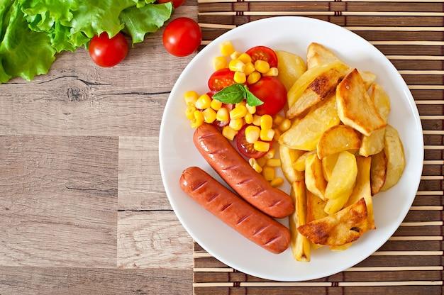 Wurst mit bratkartoffeln und gemüse auf einem teller Premium Fotos