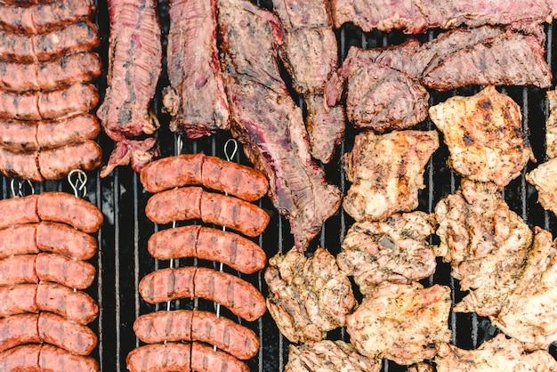 Wurst, schweinefleisch und hähnchen auf dem grill gebraten, von oben gesehen. Premium Fotos