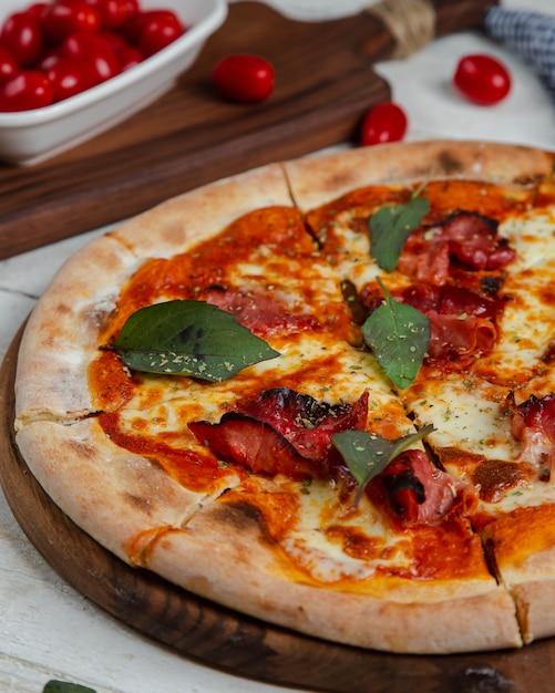 Wurstpizza garniert mit lorbeerblatt Kostenlose Fotos