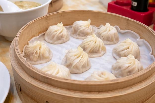 Xiao long bao suppe knödel brötchen mit stäbchen im restaurant (traditionelles chinesisches essen) Premium Fotos