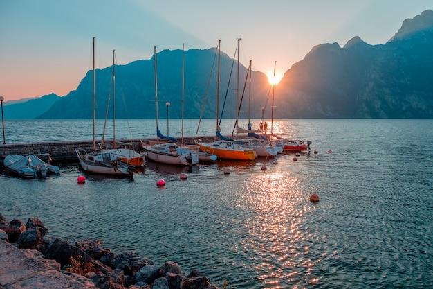 Yachten am pier während des sonnenuntergangs am gardasee. sonnenuntergang an der riva del garda. die sonne geht in den bergen unter. see im norden italiens. Premium Fotos