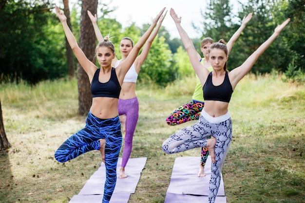 Yoga, eignung, sport und gesundes lebensstilkonzept - gruppe von personen im baum werfen auf matte draußen im park auf Premium Fotos