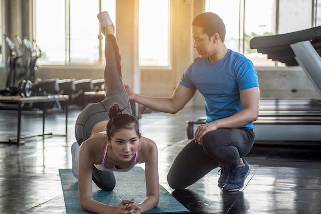 Yoga-lehrer hilft anfängern, stretching-übungen zu machen. der lehrer hilft, yoga in pose zu bringen. Premium Fotos