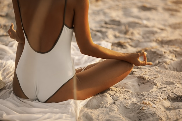 Yoga meditationspose mit kopfhörern am strand Premium Fotos