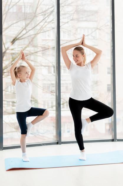 Yoga-pose mit mutter und smiley-tochter zu hause Kostenlose Fotos