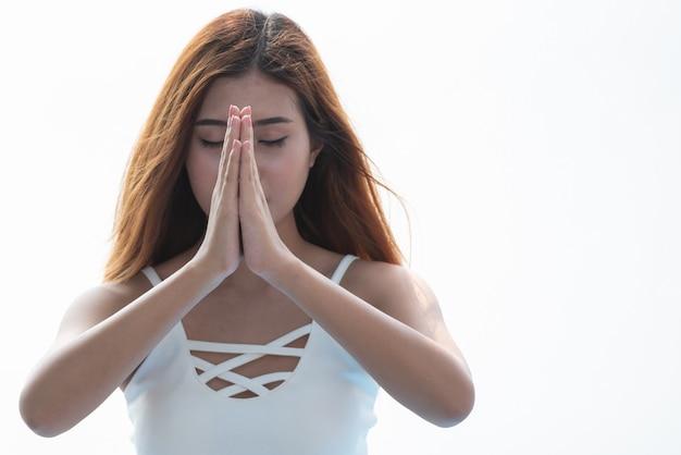 Yogafrau, die zusammen mit händchenhalten auf weißem hintergrund meditiert. Premium Fotos