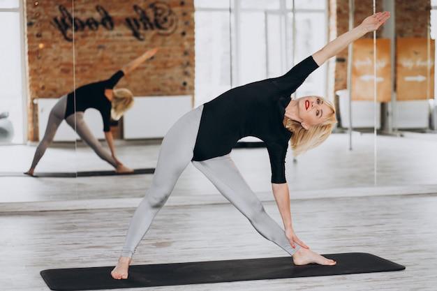 Yogalehrerin, die im fitnessstudio trainiert Kostenlose Fotos