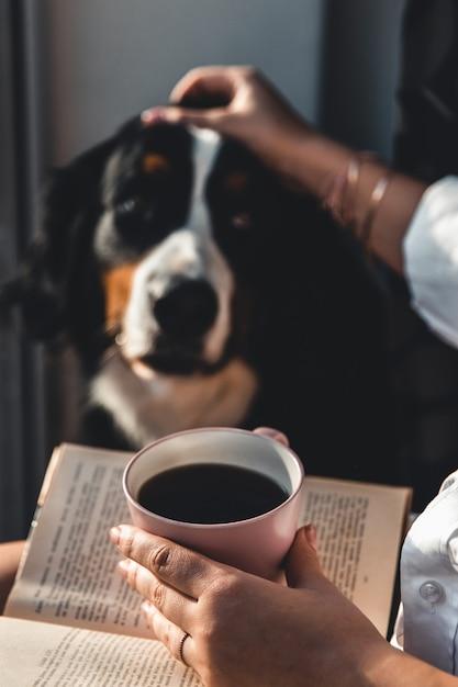 Yoman sitzt im wohnzimmer mit ihrem niedlichen berner sennenhund, liest und trinkt kaffee. Premium Fotos