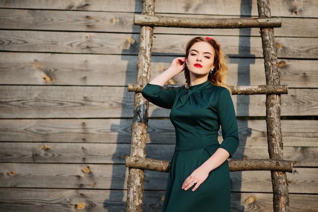 Yong-eleganzblondine am grünen kleid Premium Fotos