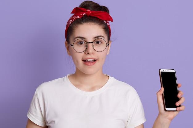 Yong hübsche frau, die isoliert über fliederraum mit aufregung steht, telefon hält, freizeitkleidung und brille trägt Kostenlose Fotos