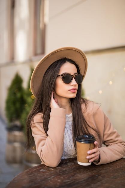 Yound fashion lady sitzt auf dem tisch im café kleider in freizeitkleidung dunkle sonnenbrille mit kaffeetasse Kostenlose Fotos