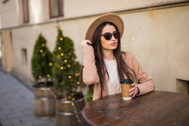 Yound model sitzt auf dem tisch in cafe kleidern in freizeitkleidung dunkle sonnenbrille mit kaffeetasse Kostenlose Fotos