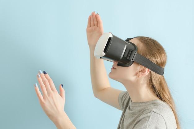 Yuong frau mit brille der virtuellen realität. blauer hintergrund Premium Fotos