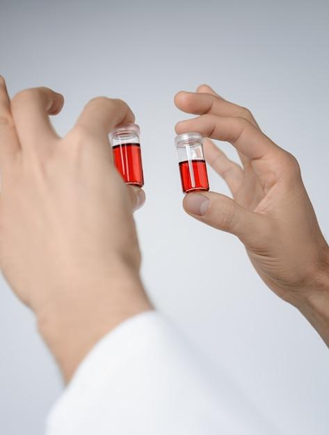 Ywo flüssige proben in männlichen händen Premium Fotos