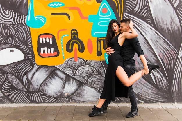Zärtliches paartanzen vor graffitiwand Kostenlose Fotos