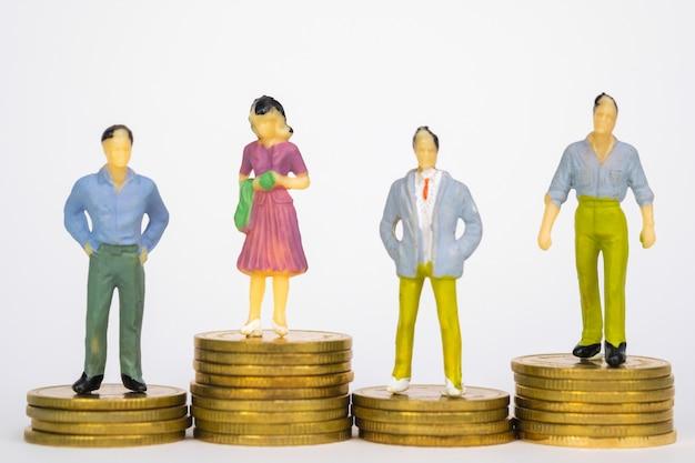 Zahl miniaturgeschäftsmann, der auf münzenstapel steht Premium Fotos