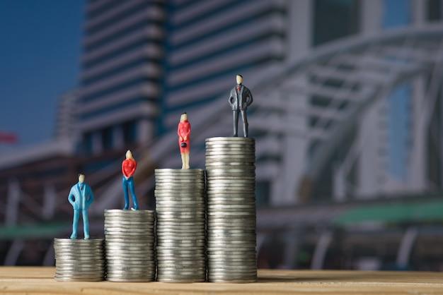 Zahl miniaturgeschäftsmann, der auf stapel der münze steht Premium Fotos