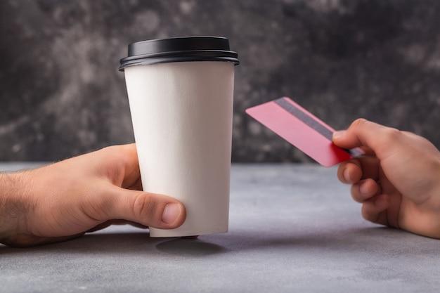 Zahlen für kaffee in der weißen schale durch rote kreditkartefrauen- und -mannhände Premium Fotos