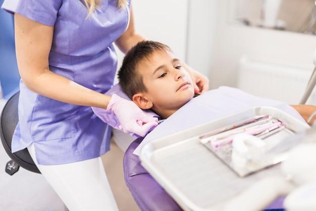 Zahnarzt, der den nahen jungen sich lehnt auf zahnmedizinischem stuhl in der klinik sitzt Kostenlose Fotos