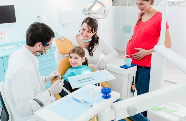 Zahnarzt, der die ganze familie in seinem büro behandelt Premium Fotos