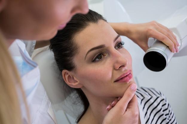 Zahnarzt, der eine zahnröntgenaufnahme einer patientin nimmt Kostenlose Fotos