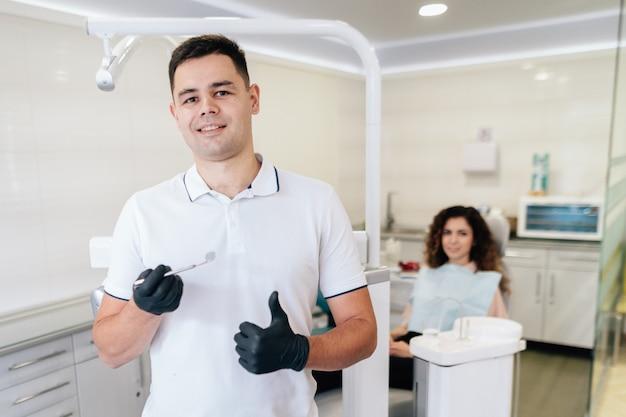 Zahnarzt, der instrument und patienten im büro hält Kostenlose Fotos