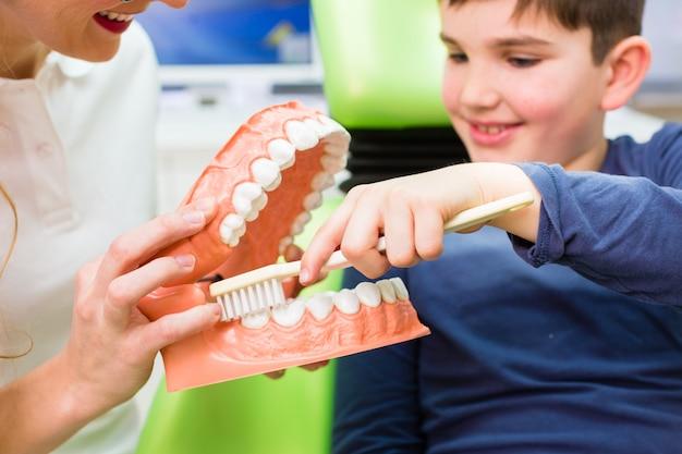 Zahnarzt, der jungenreinigungszahn erklärt Premium Fotos