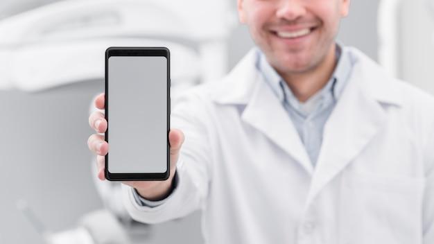 Zahnarzt, der smartphone darstellt Kostenlose Fotos