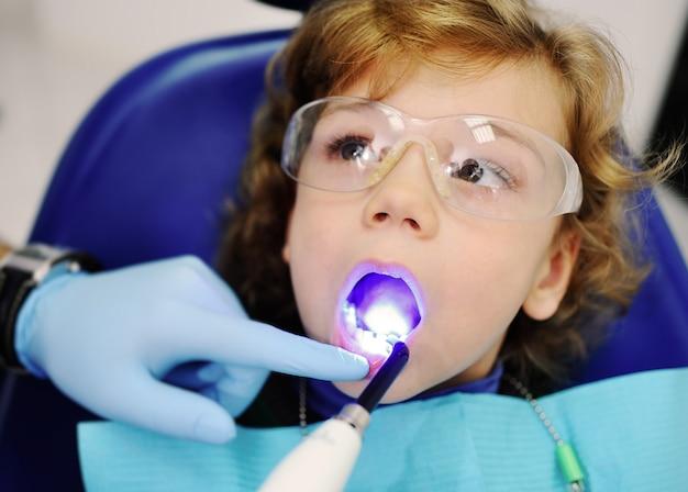 Zahnarzt glänzt auf babyzahn-speziallampe für zahnfüllungen Premium Fotos