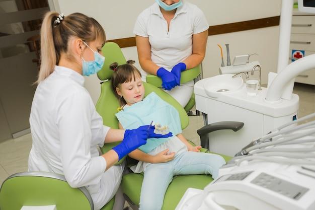 Zahnarzt und mädchen, die gebisse betrachten Kostenlose Fotos