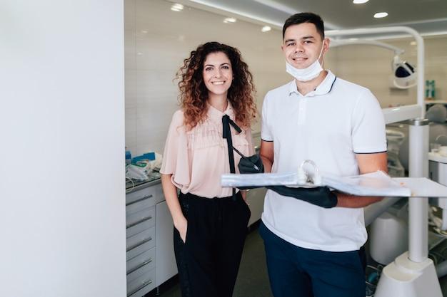 Zahnarzt und patient, die beim halten einer mappe lächeln und aufwerfen Kostenlose Fotos