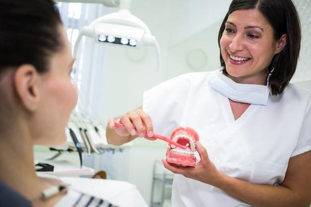 Zahnarzt zeigt dem patienten, wie man zähne putzt Kostenlose Fotos