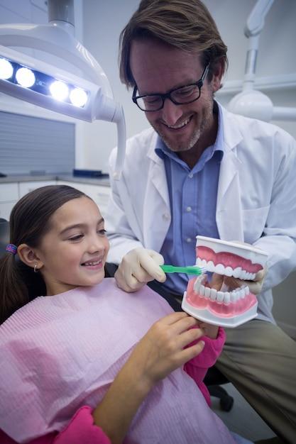 Zahnarzt zeigt jungen patienten, wie man zähne putzt Premium Fotos